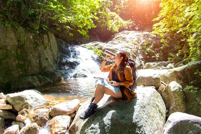 Eau potable de femme asiatique de randonneur après des jumelles de regard dans la chute de l'eau, forêt de fond photographie stock libre de droits