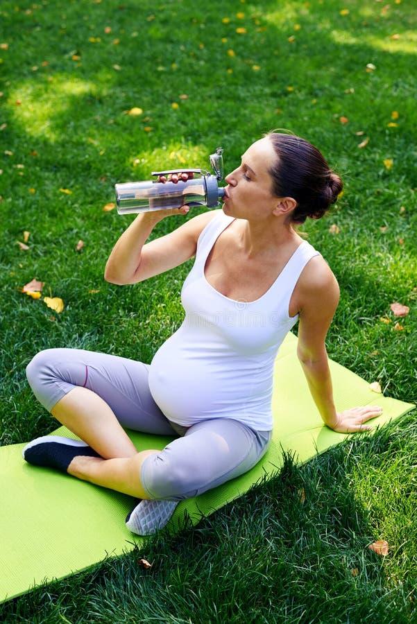 Eau potable de femme enceinte sur le tapis de yoga en parc photos stock