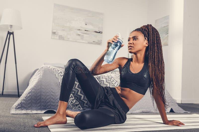 eau potable de femme folâtre d'afro-américain après séance d'entraînement à la maison image libre de droits