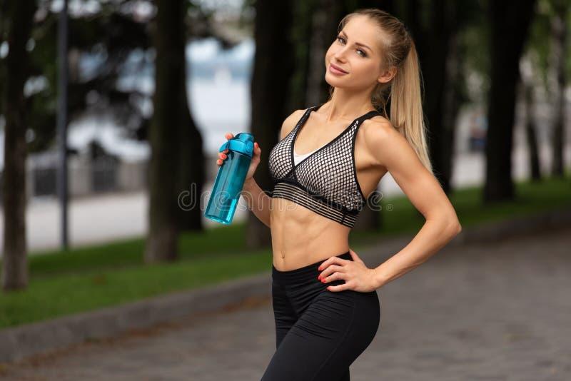 Eau potable de femme de forme physique d'une bouteille, dehors La fille active ?teint la soif photos stock