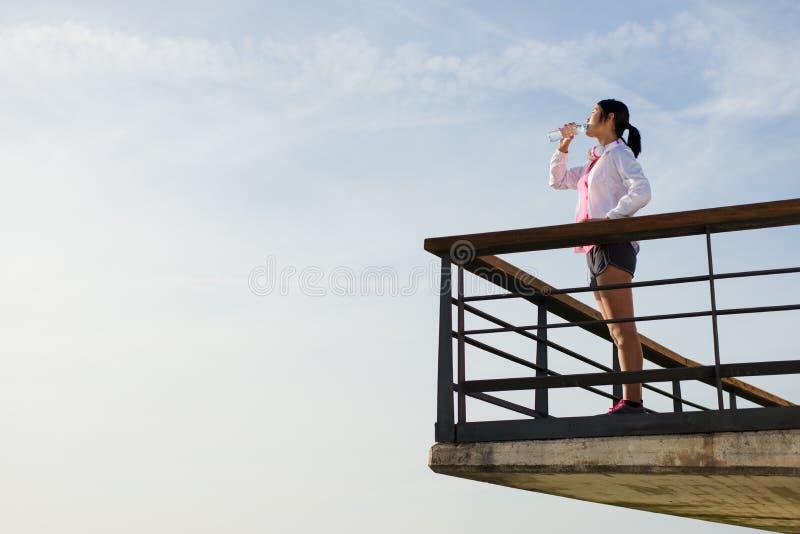Eau potable de femme sportive après séance d'entraînement image stock