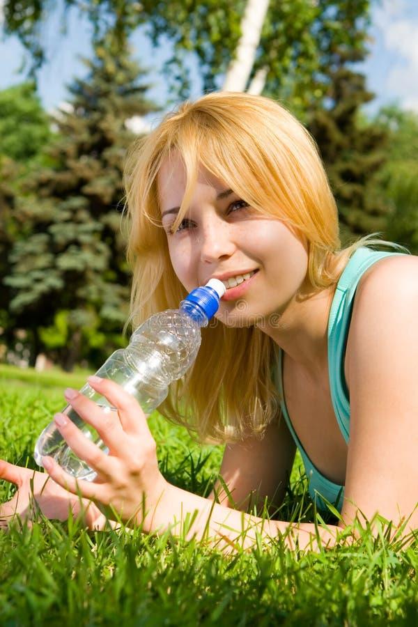 Eau potable de femme sur la clairière d'été photos stock