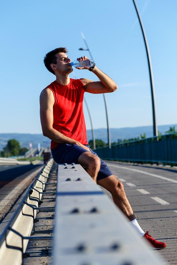 Eau potable de jeune coureur masculin et repos après séance d'entraînement de matin photo libre de droits