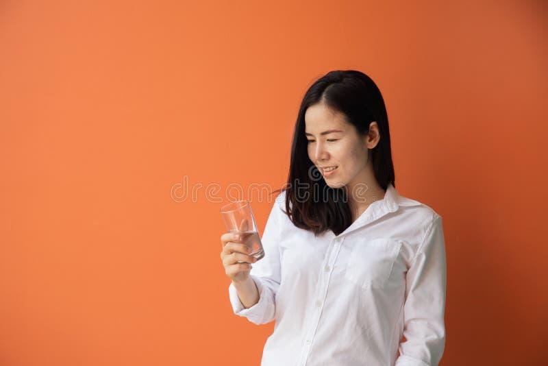 Eau potable de jeune femme asiatique sur le fond orange d'isolement images stock