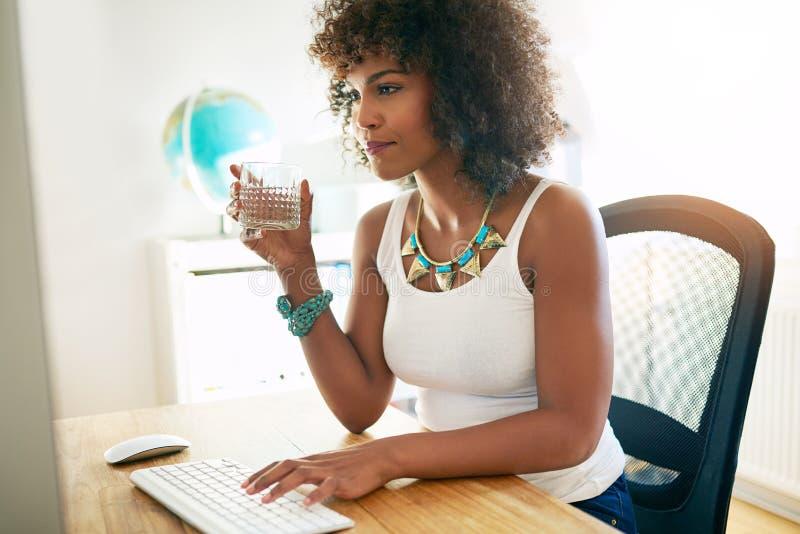 Eau potable de jeune femme d'affaires photographie stock libre de droits