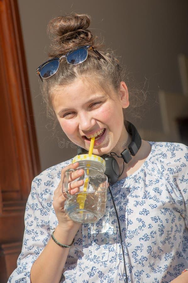 Eau potable de jeune fille d'adolescent dehors photo libre de droits