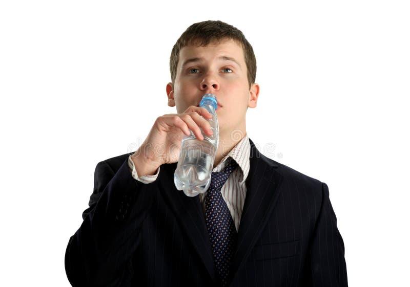 Eau potable de jeune homme d'affaires d'une bouteille image libre de droits