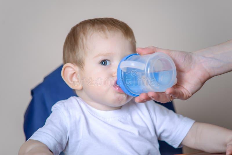 Eau potable de petit bébé garçon tout en se reposant sur une chaise dans la cuisine Maman donnant une bouteille en plastique dans photographie stock libre de droits