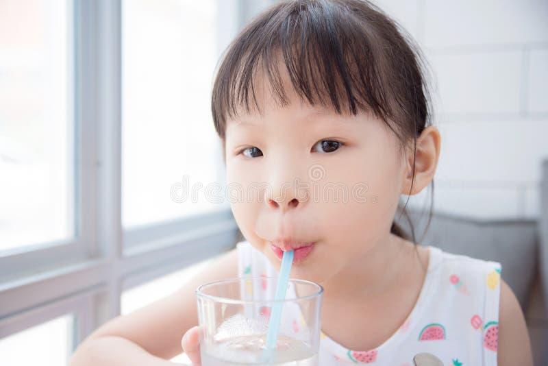 Eau potable de petite fille asiatique de verre par la paille photo stock