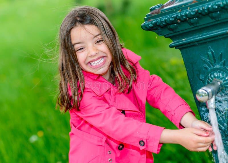 Eau potable de petite fille dans une fontaine images libres de droits