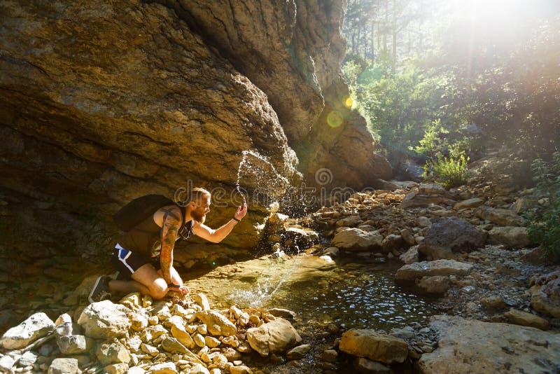 Eau potable de randonneur de la rivière L'homme apprécie l'eau non polluée fraîche propre dans la crique de montagne photos stock