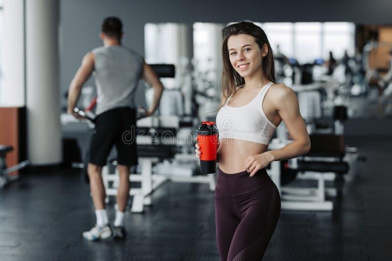 Eau potable de sourire et de fille attirante de sport tout en se tenant au gymnase avec la formation de gar?on sur le fond image stock