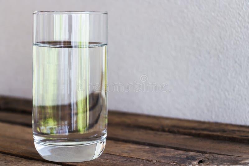 Eau potable en verre sur un plancher en bois image stock