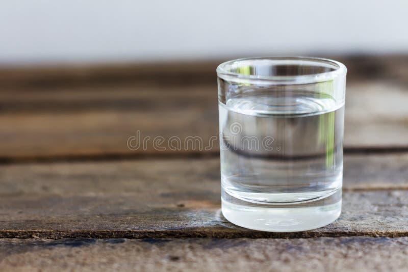 Eau potable en verre sur un plancher en bois images stock