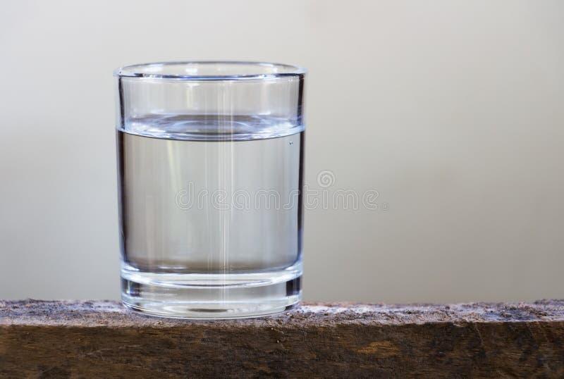 Eau potable en verre sur un plancher en bois photographie stock libre de droits