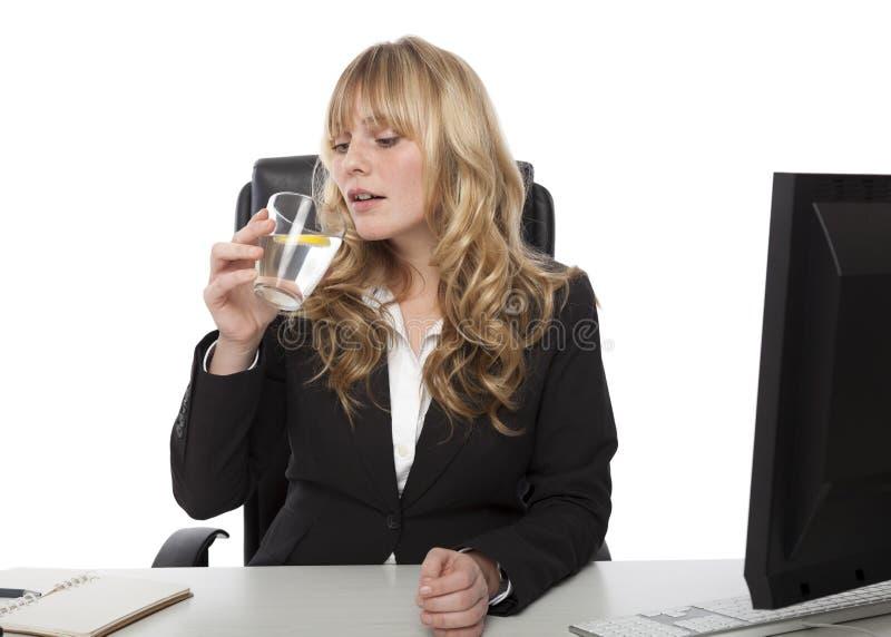 Eau potable et citron de jeune femme d'affaires photo libre de droits