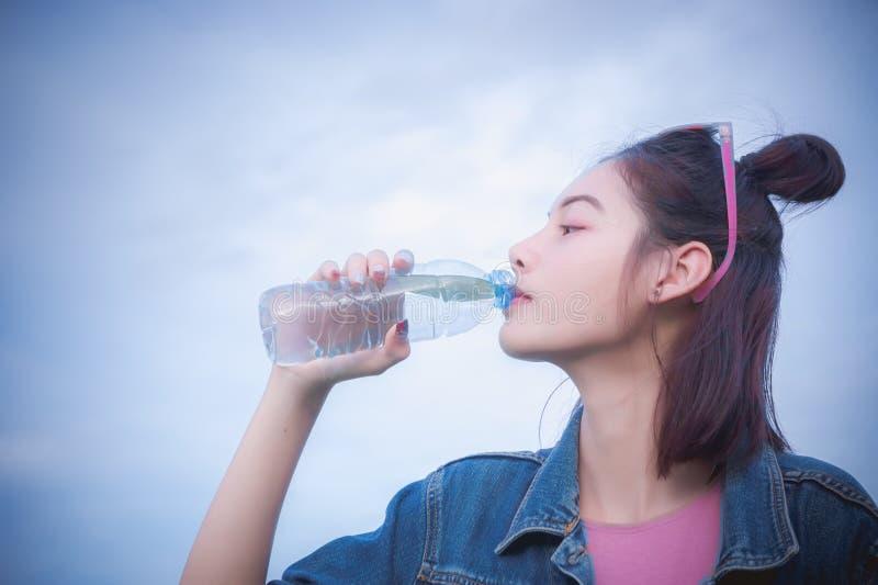 Eau potable saine du ` s de fille dans la bouteille, boisson pour assoiffé pour la régénération photos stock