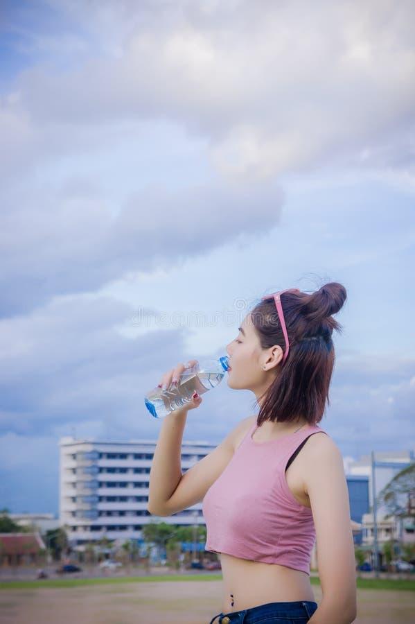 Eau potable saine du ` s de fille dans la bouteille, boisson pour le thirstil images stock