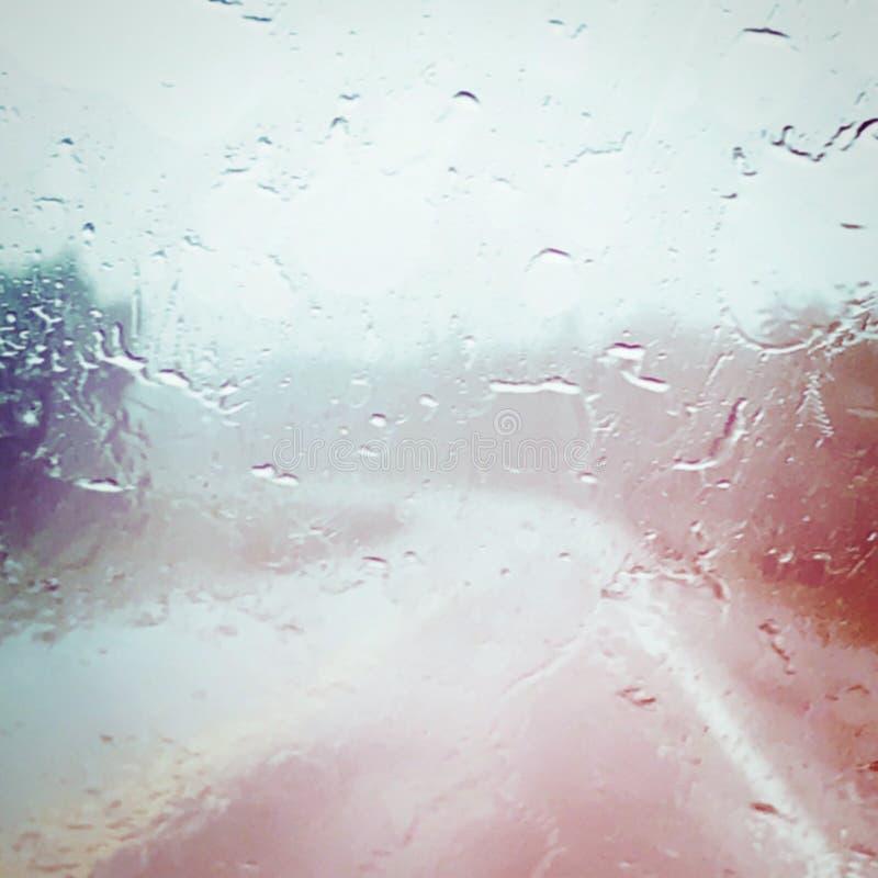 Eau sur le pare-brise de la voiture, avec vue sur la route avec effets photos libres de droits