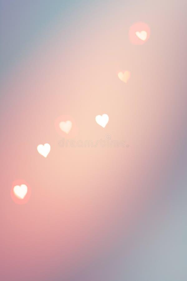 Eautifulpatroon van bokeh het fonkelen slingerlichten in hartvorm van warme roze kleur op de blauwe gradiënt van de pastelkleurwi royalty-vrije stock afbeelding