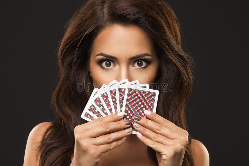 Eauty woman is hiding under playing cards,. Beauty woman is hiding under playing cards, only eyes and poker face royalty free stock photos