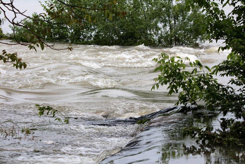 Eaux d'inondation boueuses fluides passant par-dessus le mur provisoire de protection d'inondation de sacs de sable couvert de ny photos libres de droits