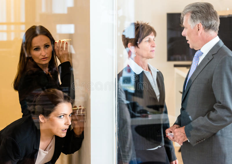 Eavesdropping in the office. Two colleagues listening with a glass to the wall of the next office room where a men and a women discuss their matters. Concept for royalty free stock photos