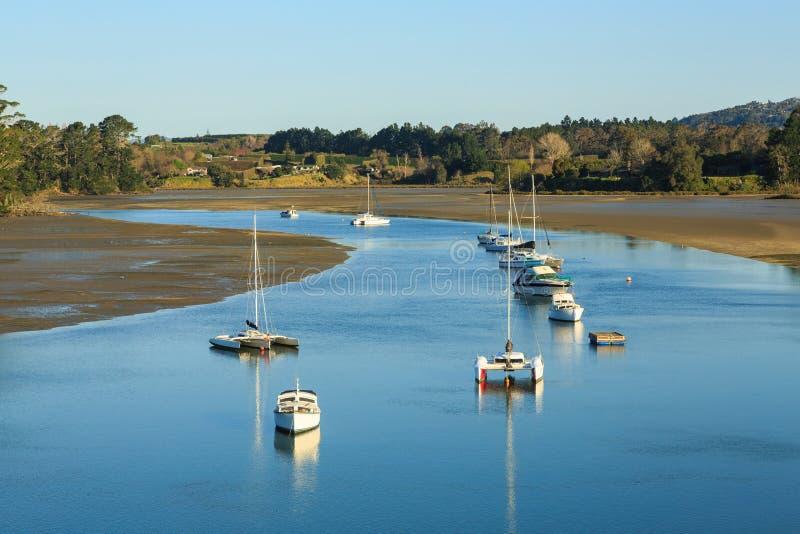 Ebbe in einem Hafen, wenn die Boote in einen Kanal schwimmen stockfotografie