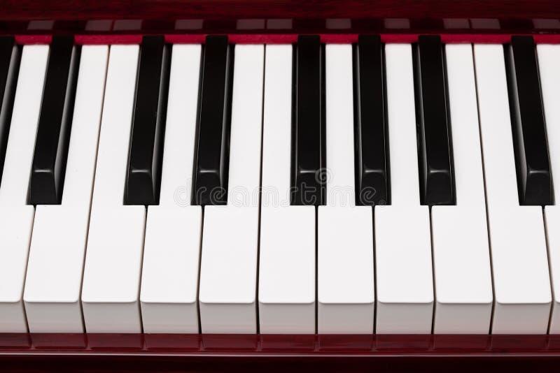 Ebbehout en ivoorsleutels van rode piano stock afbeelding