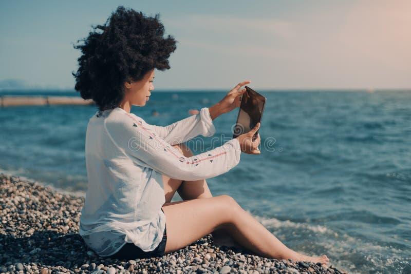 Ebbehouten meisje die selfie terwijl het zitten op strand nemen royalty-vrije stock foto's