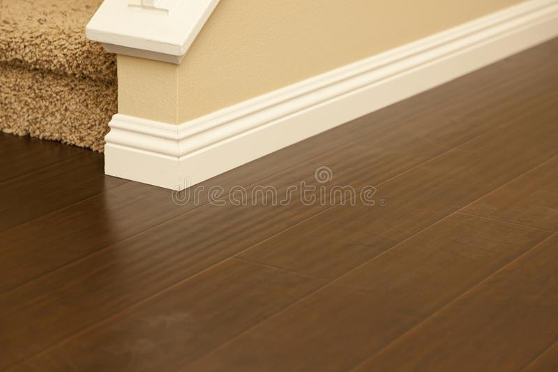 Eben installierter Brown-Laminats-Bodenbelag und Fußleisten im Haus stockbild