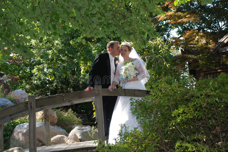 Eben Wed-Paar-Kuss auf Brücke stockfotografie