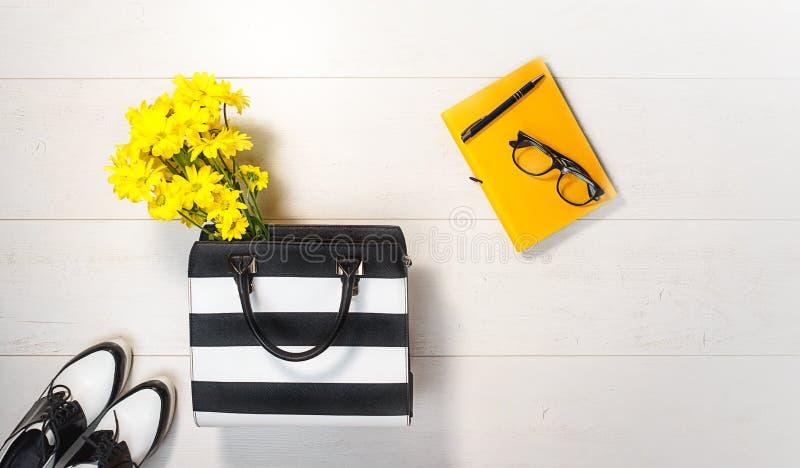 Ebene gelegte gelbe Blumen der weiblichen Geschäftszusätze auf weißem Hintergrund Weibliche Art mit Taschenschuhnotizbuch-Glassti lizenzfreie stockbilder