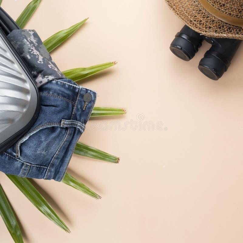 Ebene gelegter grauer Koffer mit Ferngläsern, Hut, Jeans auf Pastellhintergrund Reisekonzept - Bild lizenzfreie stockbilder