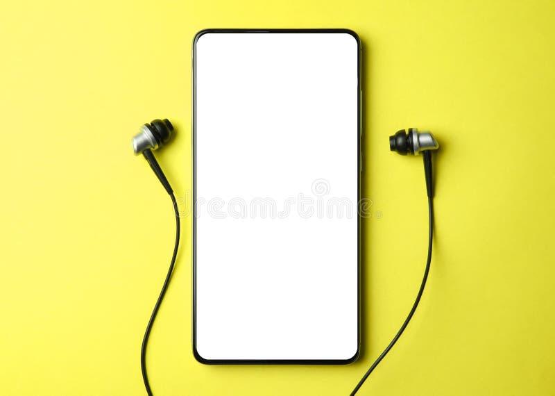 Ebene gelegtes intelligentes Telefon, beweglich mit Kopfhörern auf einem rosa Hintergrund, Kopienraum lizenzfreies stockfoto