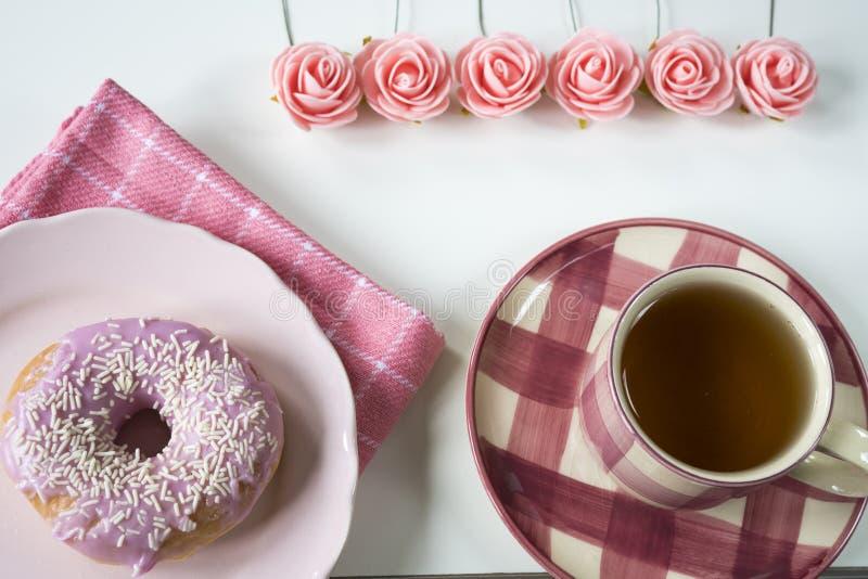 Ebene gelegtes rosa Frühstück mit Rosen, Tasse Tee, Serviette und Donut auf Platte stockfoto