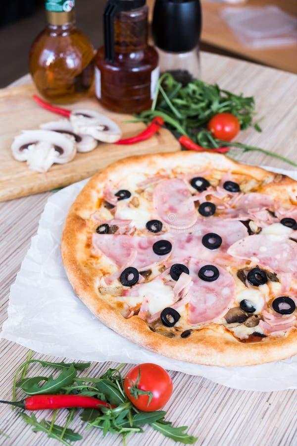 Ebene legen mit traditioneller italienischer Pizza mit Schinken und Oliven auf schwarze Steintabelle und verschiedene Bestandteil lizenzfreie stockbilder