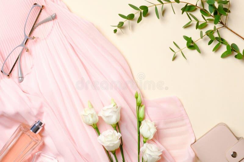 Ebene legen weibliche Zusätze, Parfümflasche, Blumen der weißen Rosen, rosa Kleid, Gläser Draufsichtschönheit Bloggerschreibtisch lizenzfreies stockbild