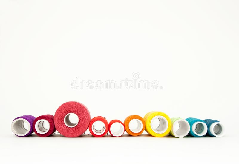 Ebenenlage mit bunten Baumwollfadenspulen, Stickgarn, Regenbogenspulen, Spott oben, Draufsicht Planmodell auf leerem Wei? stockfotografie