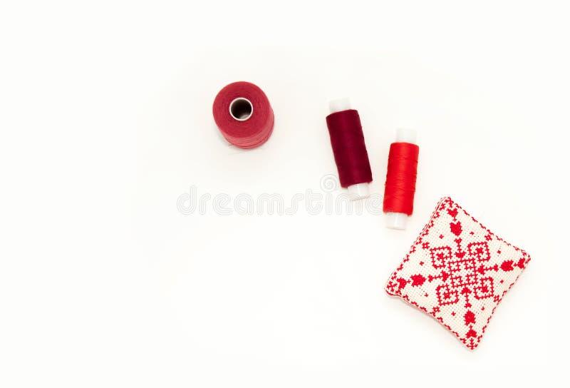 Ebenenlage mit handgemachter roter gestickter Nadelauflage, Fadenspulen, Stifte, Nadeln, Spott oben, Draufsicht Planmodell auf le stockfoto