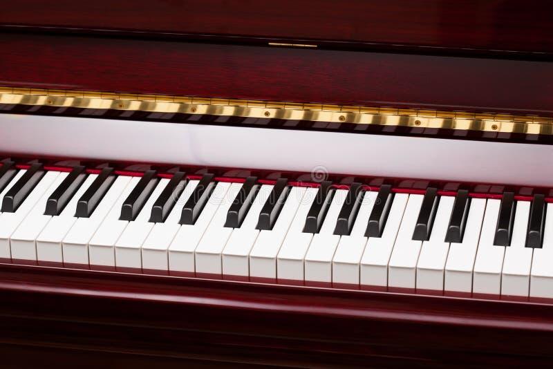 Ebenholts- och elfenbentangenter av det röda pianot royaltyfri foto