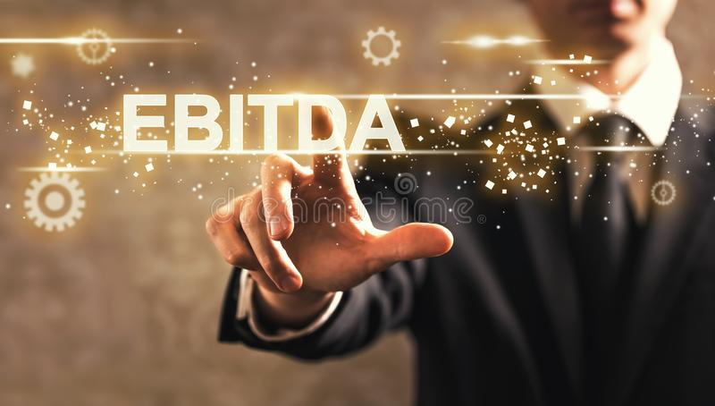 EBITDA text with businessman. On dark vintage background stock photo