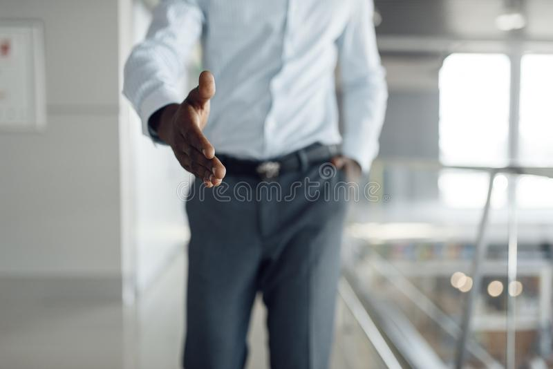 Ebony businessman holds out his hand in mall royalty free stock photography