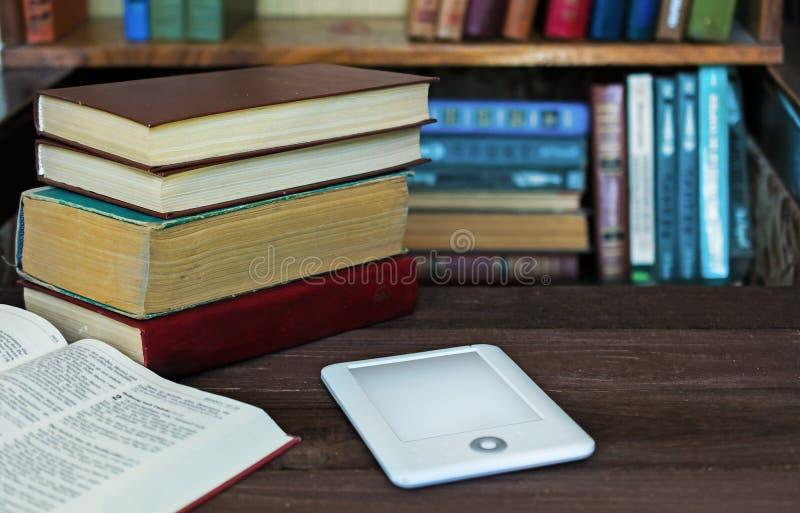 Ebook和旧书在桌上有书架背景 免版税图库摄影