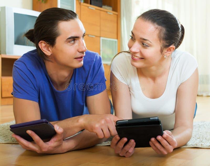从eBook屏幕的夫妇读书 免版税图库摄影
