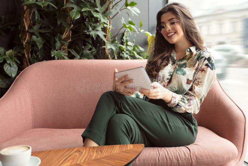 Ebook alegre de la lectura de la mujer en el café foto de archivo