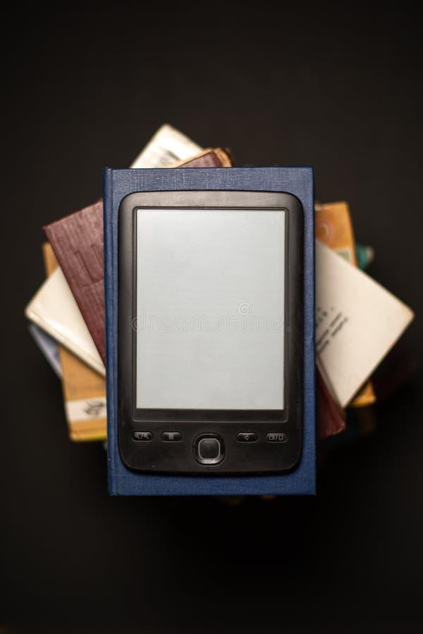EBook auf einem Stapel gewöhnlichen Papierbüchern lizenzfreies stockbild