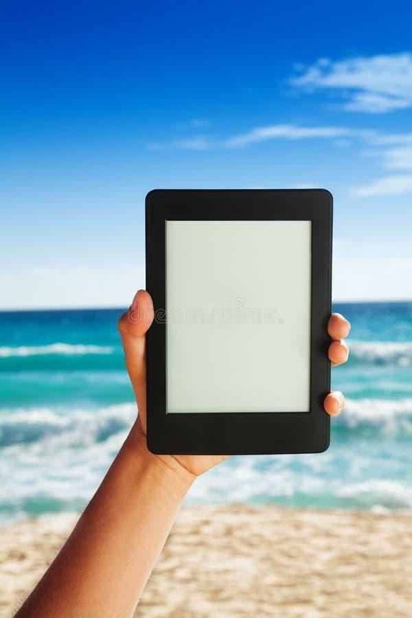 Ebook auf Strandhintergrund lizenzfreies stockbild