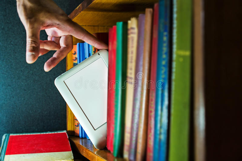 Ebook choice among paper books. new technology concept. Man choose ebook among paper books. new technology concept stock image