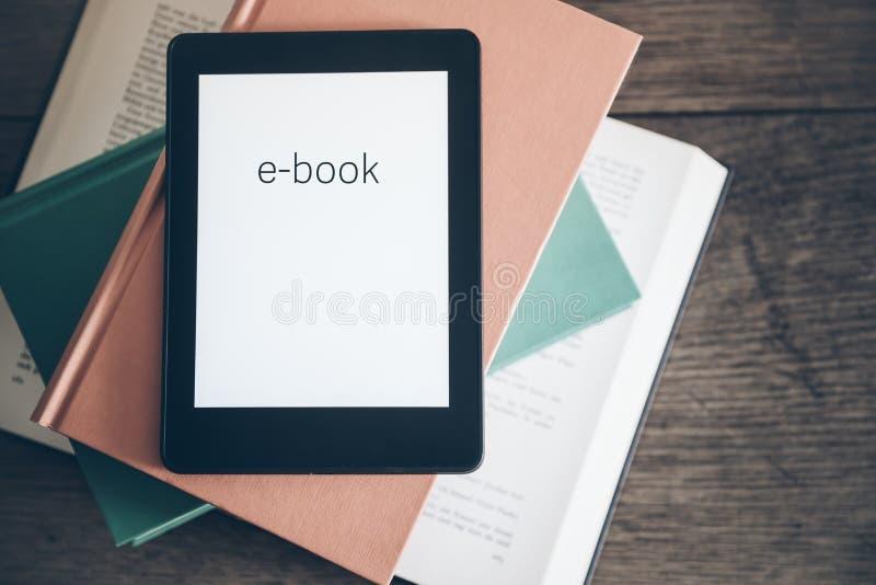 EBook czytelnik na stercie książki zdjęcia stock